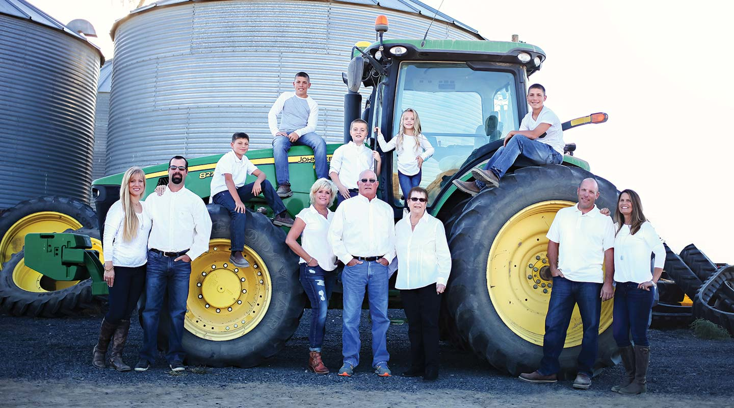 All 12 members of the Berg family posed around a John Deere tractor
